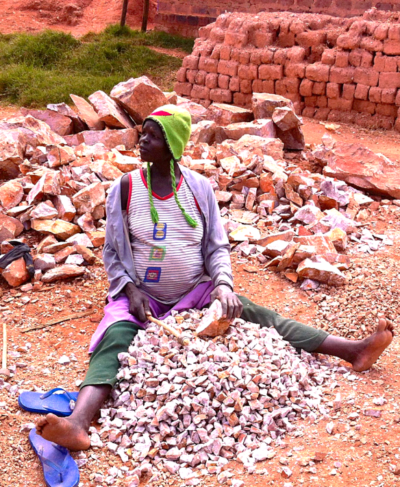 A heavily pregnant woman spends her day pounding larger stones into gravel. Most residents are paid by the kilo for their work.