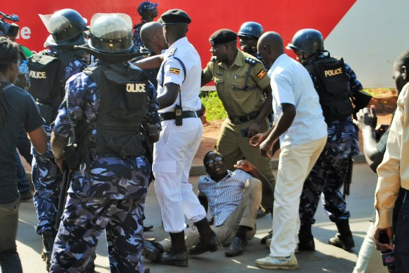 Police and Mbabazi supporters stumble into traffic while in the midst of a physical fight.